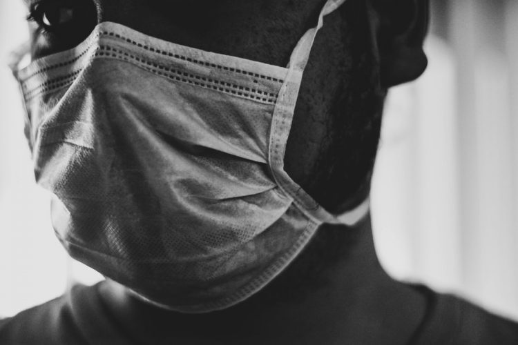 Grocery worker and customer wearing mask to protect from coronavirus spread